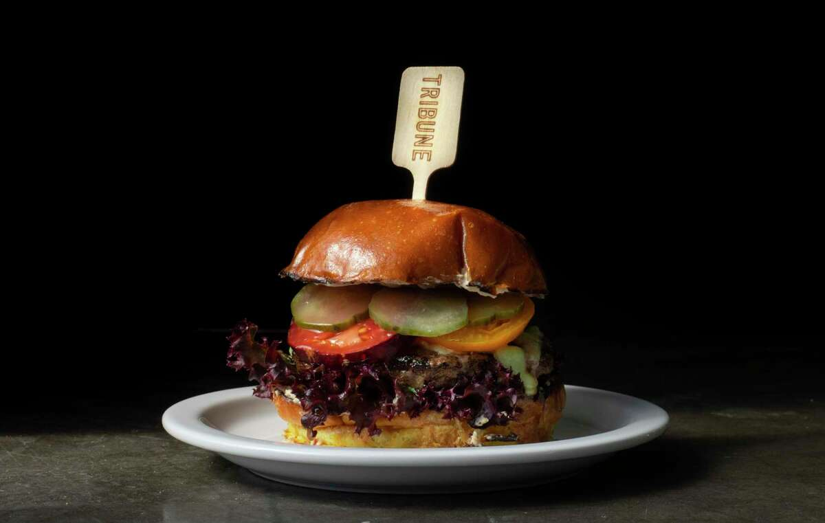 The burger at Oakland restaurant Tribune features an 8-ounce patty and red onion schmear on a sweet potato bun.