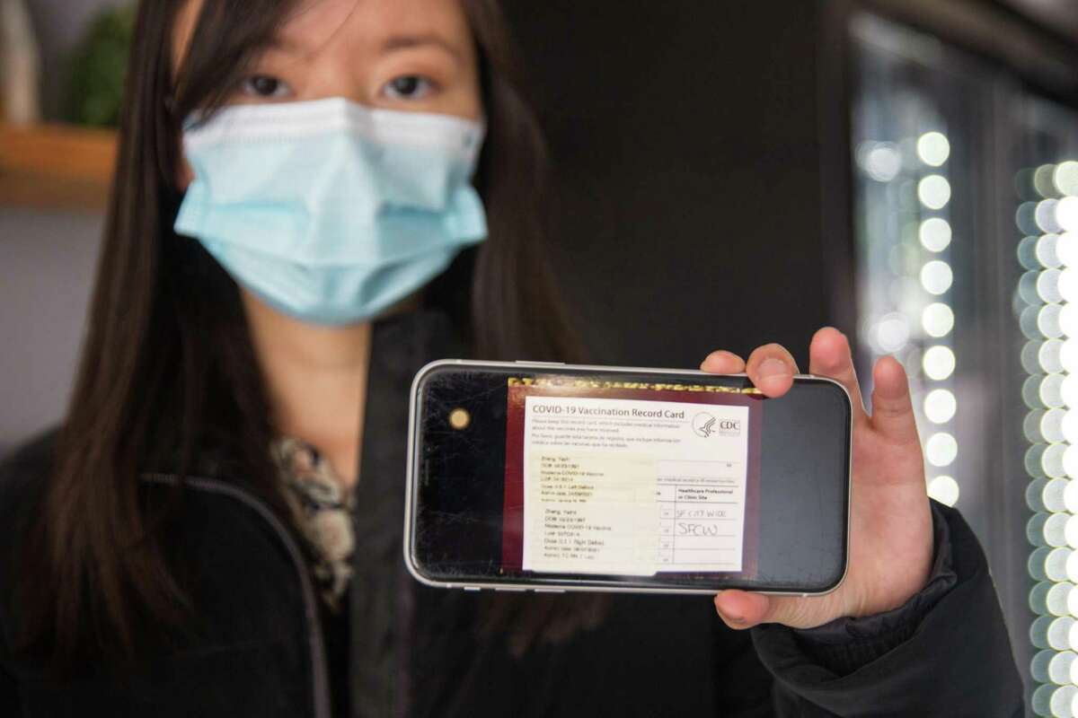 Yazhi Zheng poses with a copy of her vaccination card loaded on her phone at Vegan Picnic restaurant where the proof of vaccination is now required from costumers. In San Francisco, Calif. On Thursday, August 5, 2021.
