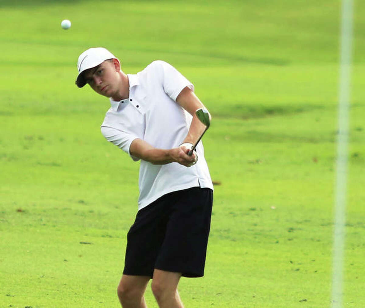 EA-WR's Carson Reef chips toward the pin on hole No. 2 at the Hickory Stick Invite on Monday at Belk Park in Wood River.