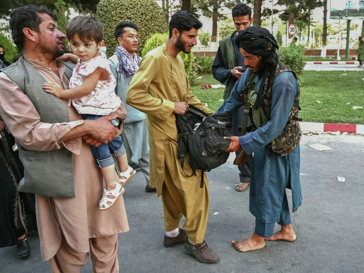 A Taliban fighter (right) searches the bags of people coming out of the Kabul airport in Kabul on August 16, 2021, after a stunningly swift end to Afghanistan's 20-year war, as thousands of people mobbed the city's airport trying to flee the group's feared hardline brand of Islamist rule. (Wakil Kohsar/AFP via Getty Images/TNS)