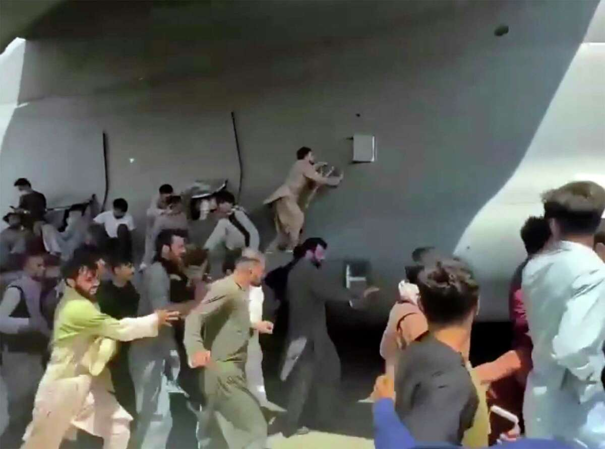 Afghans run alongside a U.S. Air Force transport plane in Kabul on Monday in a desperate attempt to escape the Taliban.