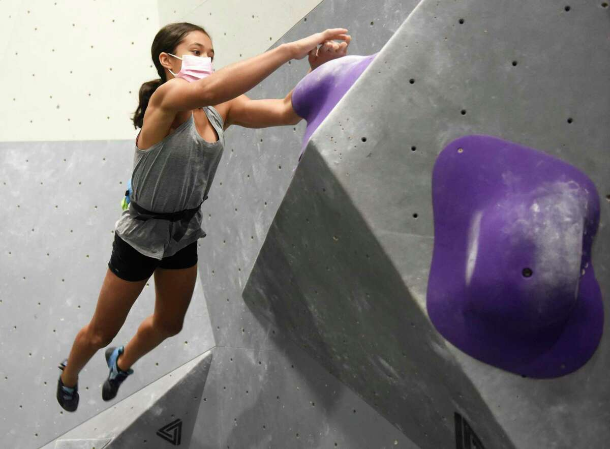 Sienna Perez, 14, leaps on the rock wall at Beta Climbing + Fitness in Stamford Monday.