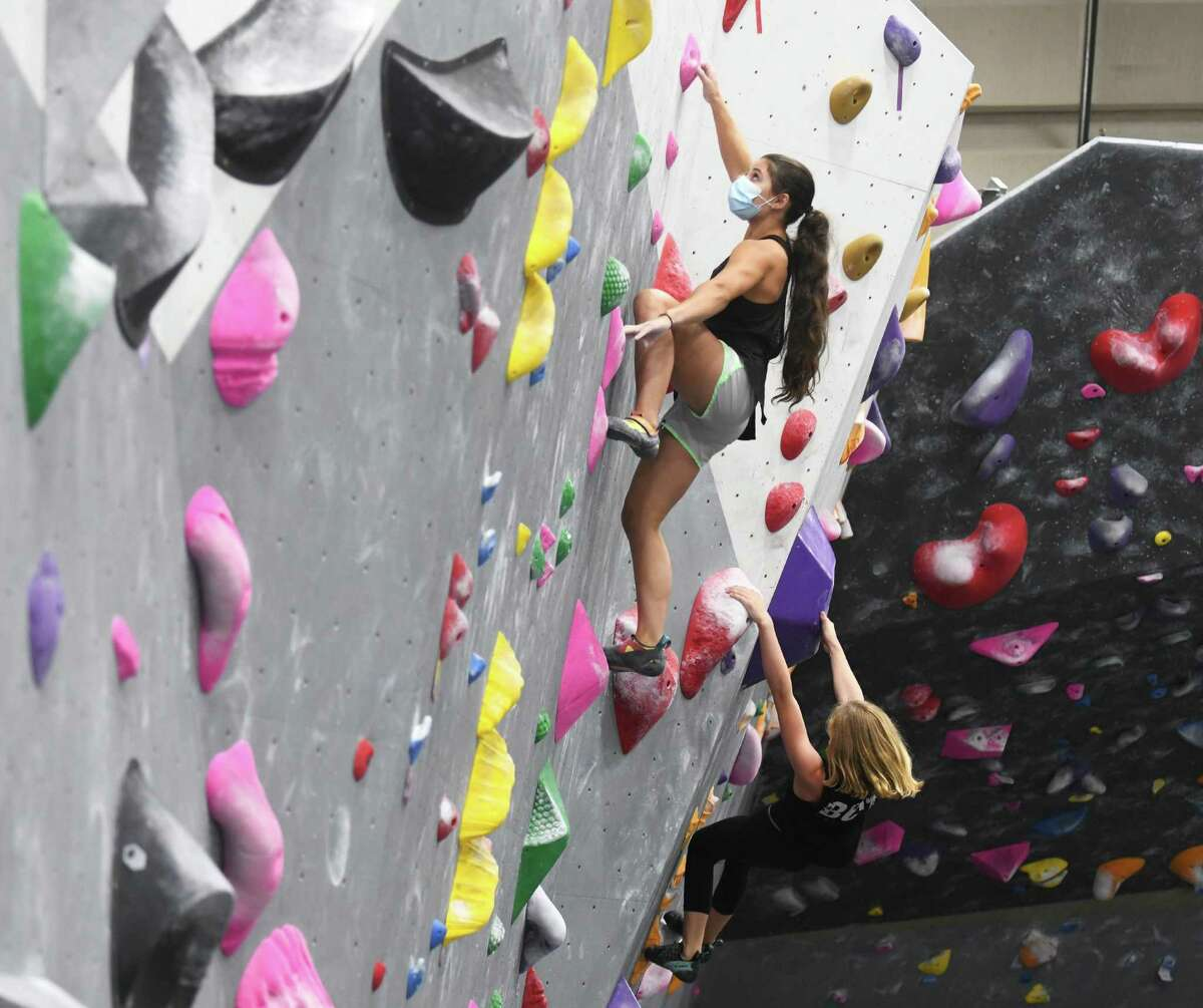 Elizabeth Astorina, 15, climbs the rock wall at Beta Climbing + Fitness in Stamford on Monday. Local climbing gyms have seen a recent uptick in participation following the sport's debut at the Olympics.
