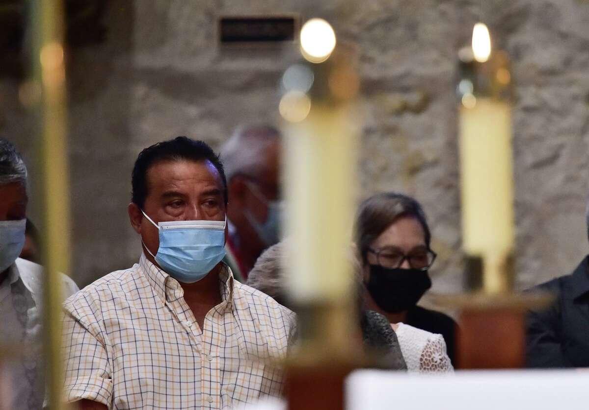 Worshipers wear masks and pray Sunday at San Fernando Cathedral.