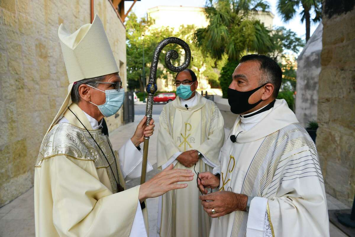 Archbishop Gustavo Garcia-Siller (left) talks with the Very Rev. Carlos B. Velazquez (right) and Deacon Roger Macias (center) before a Sunday mass at San Fernando Cathedral.