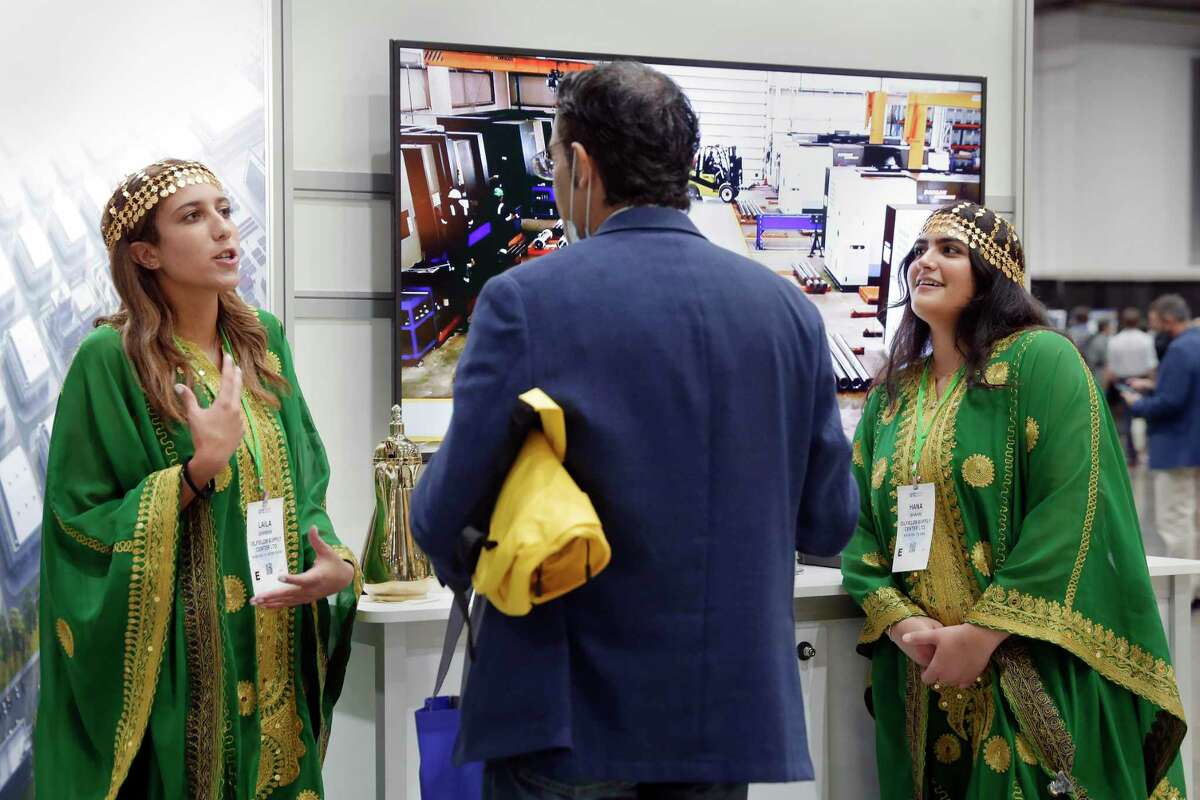Dressed in a traditional Saudi costume, Laila Darwish, left, and Hana Shahin, right, with Oilfields Supply Center Ltd., talk with a conference attendant as they hand out drinks and treats at their booth during day 1 of the Offshore Technology Conference, held at the NRG Center Monday, Aug. 16, 2021 in Houston, TX.