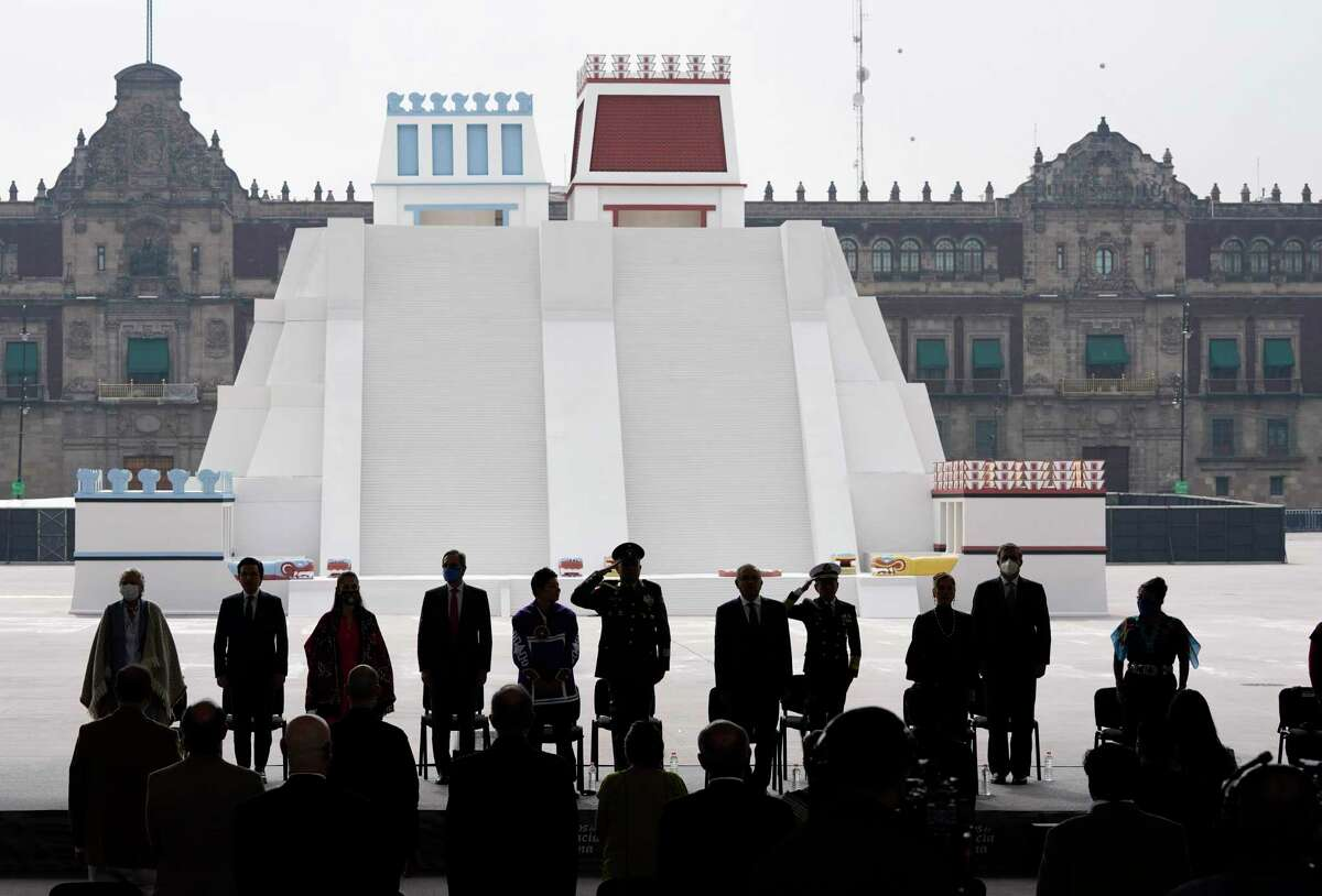 Mexican President Andres Manuel Lopez Obrador, center right, and officials, stand in front of a replica of the Aztec Templo Mayor, during a ceremony to commemorate the 500th anniversary of the fall of the Aztec empire capital of Tenochtitlan, known today as Mexico City, in Mexico City's main square the Zocalo, Friday, Aug. 13, 2021. (AP Photo/Eduardo Verdugo)