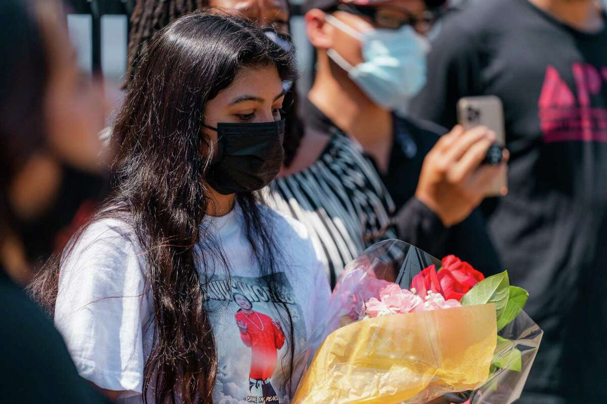A woman holds a bouquet of flowers during a press conference at the site of Erik Salgado's killing in Oakland.