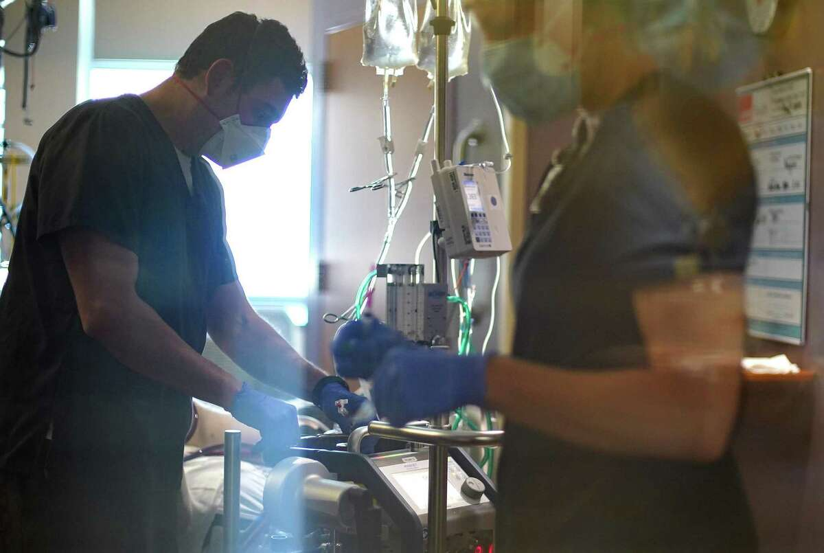 Nurses work on a COVID-19 patient, who is in his 20s, at UTMB Galveston's ICU on Wednesday, Aug. 11, 2021.