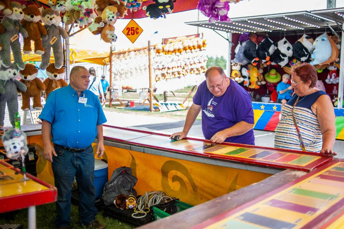 People enjoy games and food during the Midland County Fair on Aug. 16, 2021. People also tended to animals for the fair's 4-H competitions.