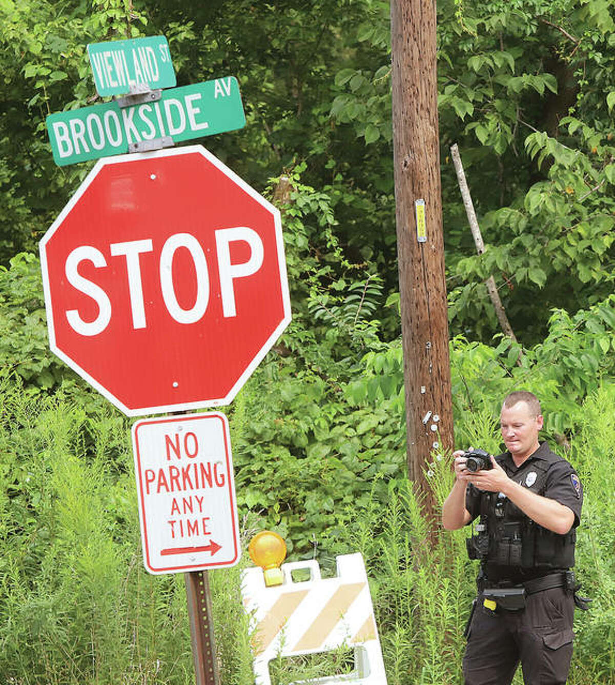 An Alton police officer takes pictures of the intersection of Viewland and Brookside streets Monday afternoon.