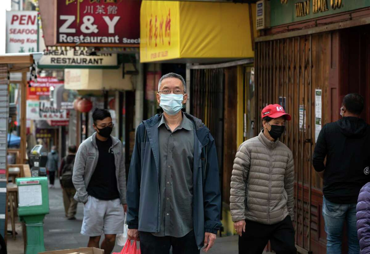 John Wang walks by former workplace Z & Y Restaurant while running errands in San Francisco's Chinatown. He was a leader in organizing workers, eventually winning a $1.61 million settlement.