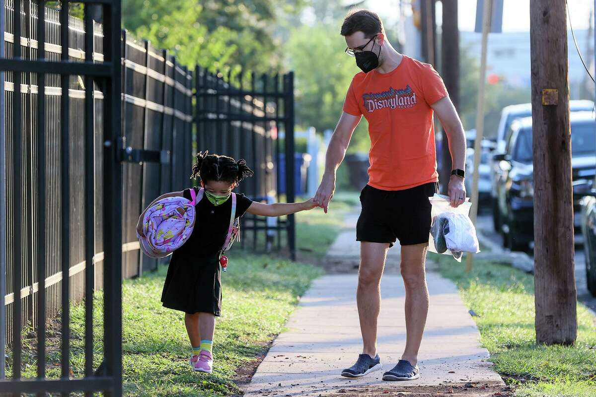 Corey Barnard walks his 4-year-old daughter Henrietta to SAISD's Advanced Learning Academy at Euclid on Monday. The district said it plans to keep its mask mandate regardless of what the courts do to Metro Health's order requiring the same.