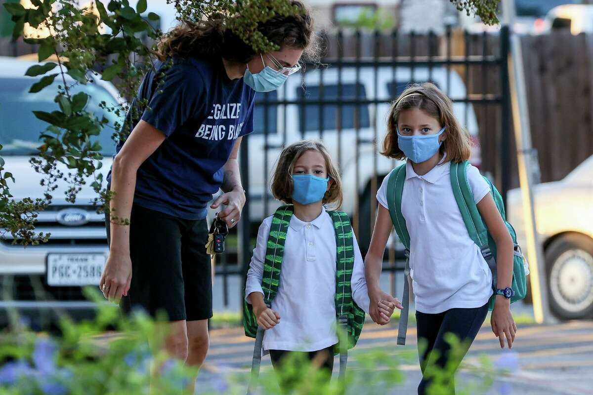 Alex Gallin-Parisis takes her daughters, Zelda, 8, right, and Gertrude, 5, to school at SAISD's Advanced Learning Academy at Euclid on Monday.