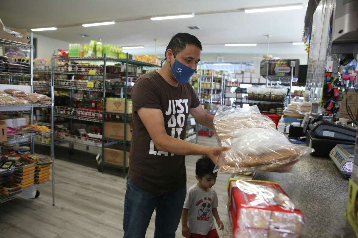 Safiullah Noorzad, of Fremont, shops for groceries at Maiwand with his son Mohammad Noorzad, 2, on Monday in Fremont. Noorzad is originally from Kabul and feels the situation has been getting worse everyday for his father, mother and soother family members who still live in Kabul.