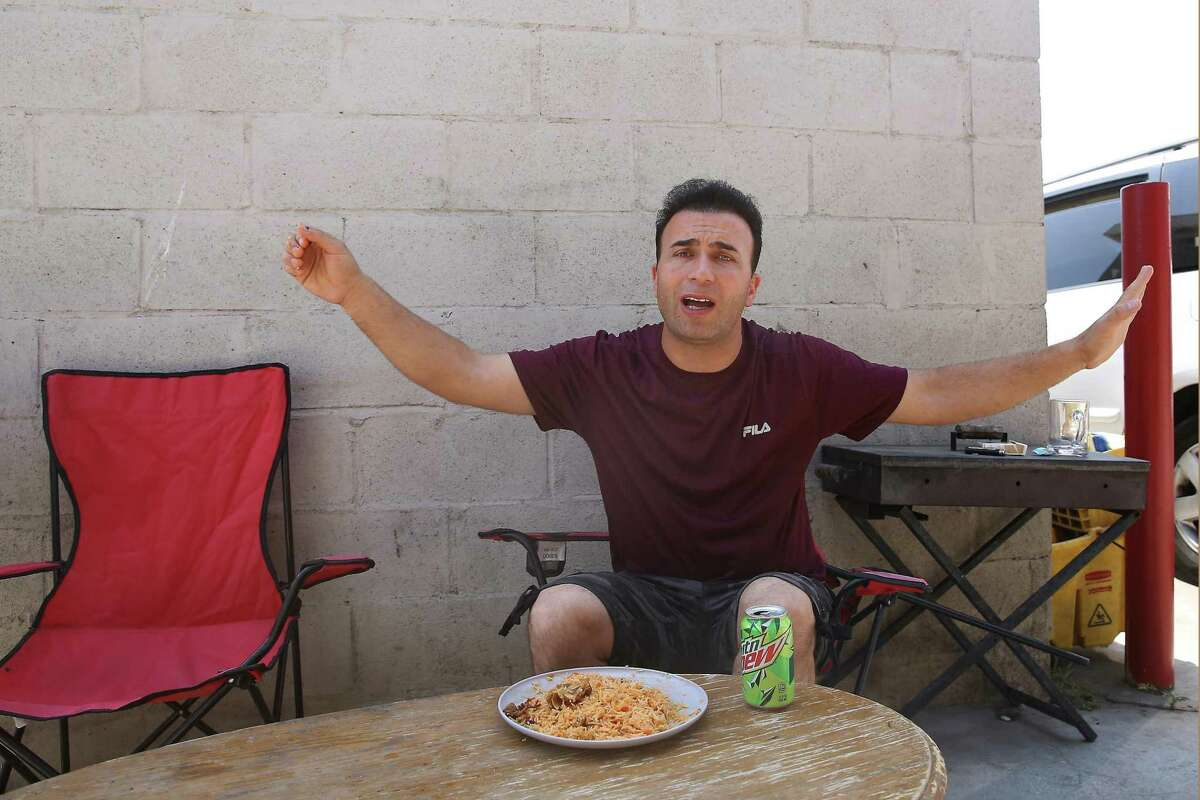 Najib Kohistani, of Fremont, reacts as he talks about his family still living in Afghanistan while eating lunch behind Khorasan Market in Fremont.