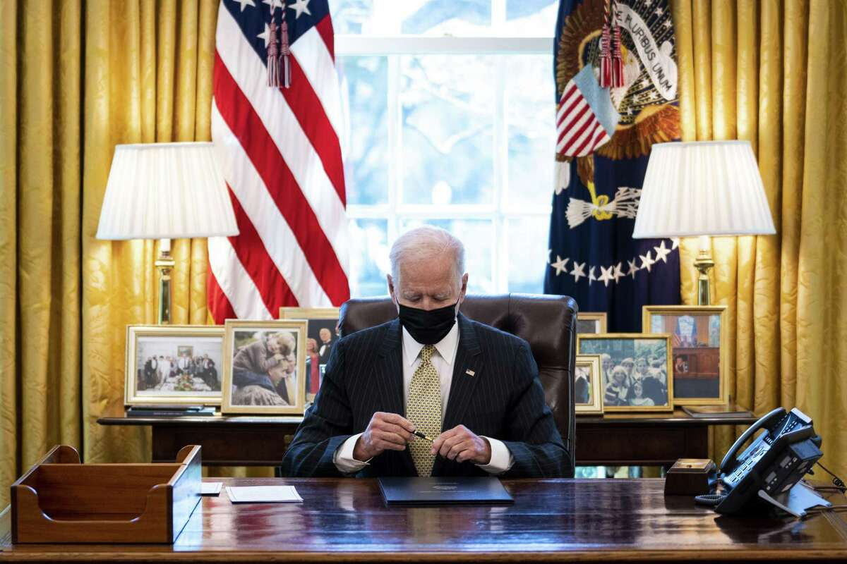 U.S. President Joe Biden wears a protective mask while signing the Paycheck Protection Program (PPP) Act in the Oval Office of the White House in Washington, D.C., U.S., on Tuesday, March 30, 2021. The Senate last week approved a two-month extension of a popular U.S. small-business relief program that still has about $79 billion left to distribute, giving companies until the end of May to apply for the forgiv