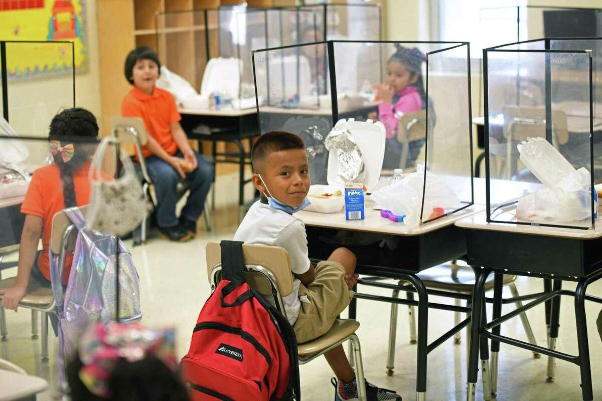 Estudiantes en toda la ciudad regresaron a su primer día de clases, portando cubrebocas. En la fotografía aparecen alumnos de la escuela primaria McDonell Elementary durante el almuerzo dentro de su salón de clases, el lunes 16 de agosto de 2021.