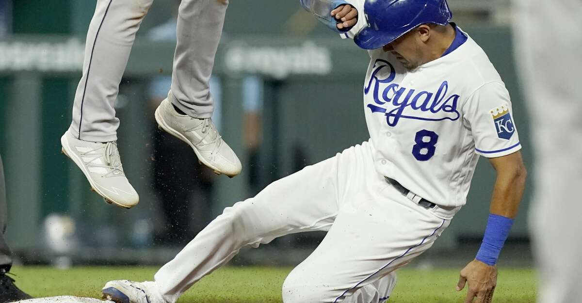 Kansas City Royals' Nicky Lopez slides under Houston Astros third baseman Aledmys Diaz to steal third during the seventh inning of a baseball game Monday, Aug. 16, 2021, in Kansas City, Mo. (AP Photo/Charlie Riedel)