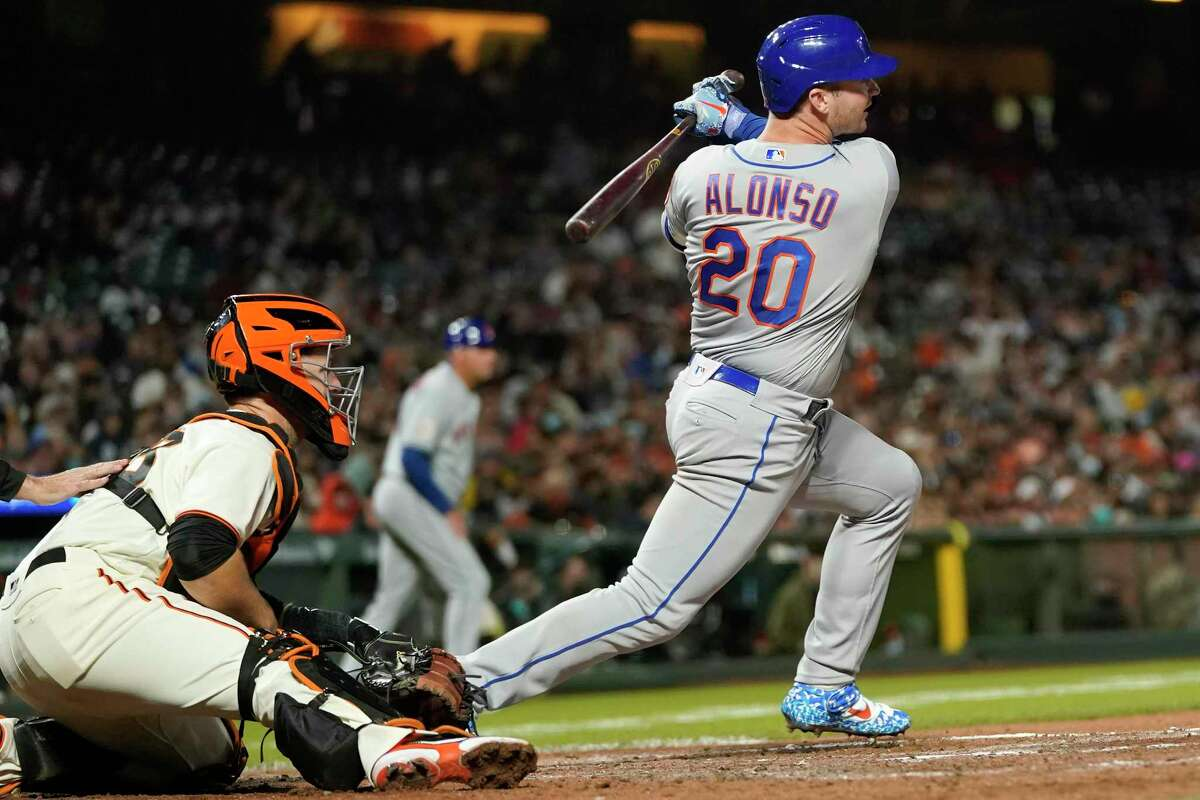 New York Mets' Pete Alonso (20) hits a two-run triple in front of San Francisco Giants catcher Buster Posey during the fifth inning of a baseball game in San Francisco, Monday, Aug. 16, 2021. (AP Photo/Jeff Chiu)