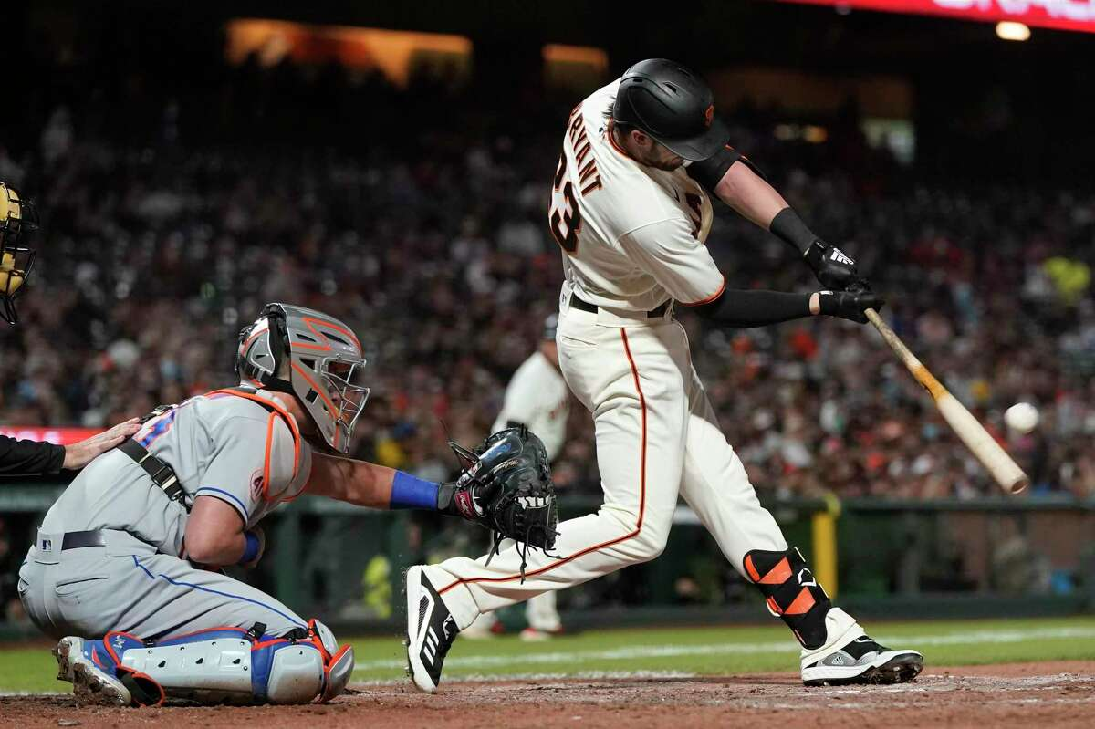 San Francisco Giants' Kris Bryant, right, hits a two-run home run in front of New York Mets catcher James McCann during the fifth inning of a baseball game in San Francisco, Monday, Aug. 16, 2021. (AP Photo/Jeff Chiu)