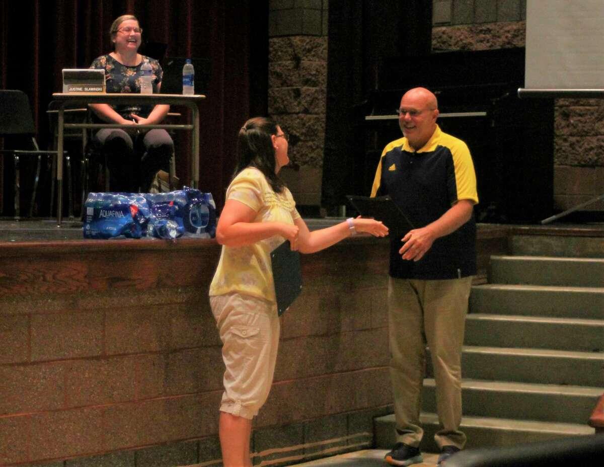 Rachel Edmondson, Manistee Area Public Schools language arts teacher, receives a certificate from superintendent Ron Stoneman during a school board meeting Wednesday for earning tenure. (Kyle Kotecki/News Advocate)