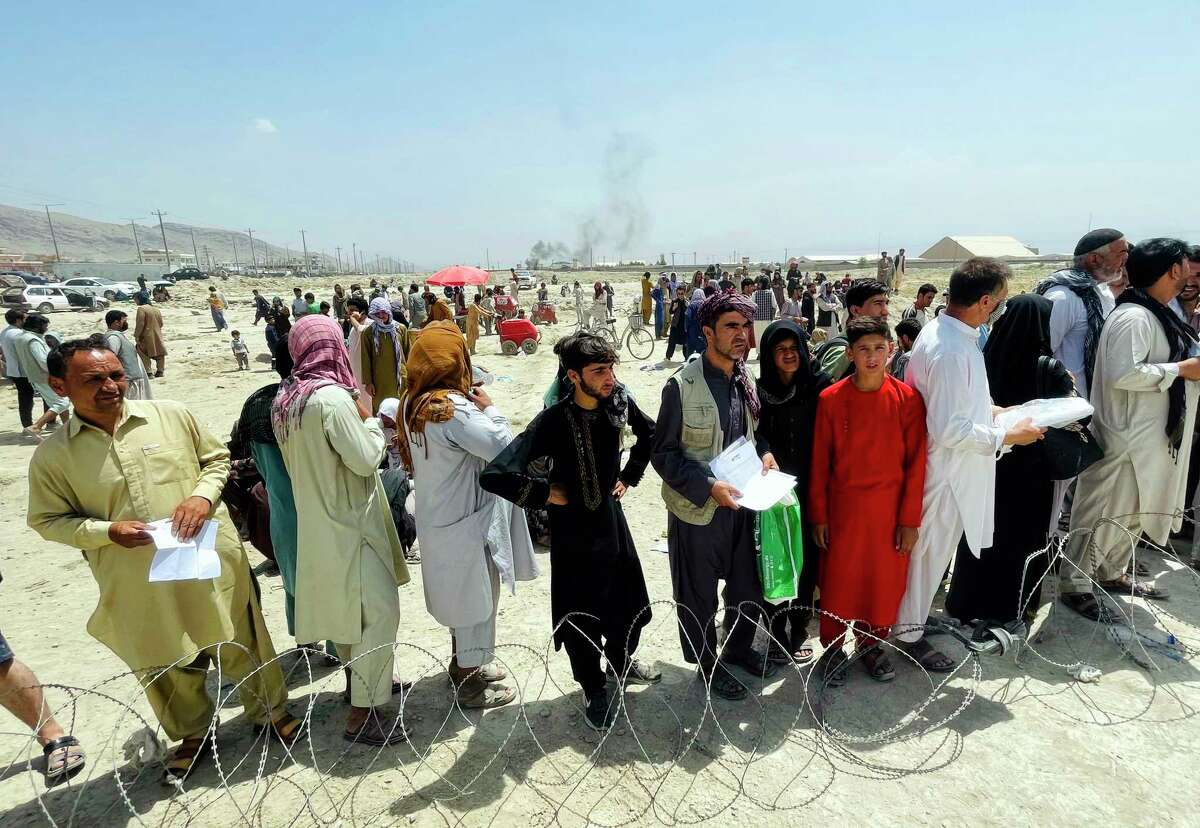 """Hundreds of people gather outside the international airport in Kabul, Afghanistan, Tuesday, Aug. 17, 2021. The Taliban declared an """"amnesty"""" across Afghanistan and urged women to join their government Tuesday, seeking to convince a wary population that they have changed a day after deadly chaos gripped the main airport as desperate crowds tried to flee the country."""