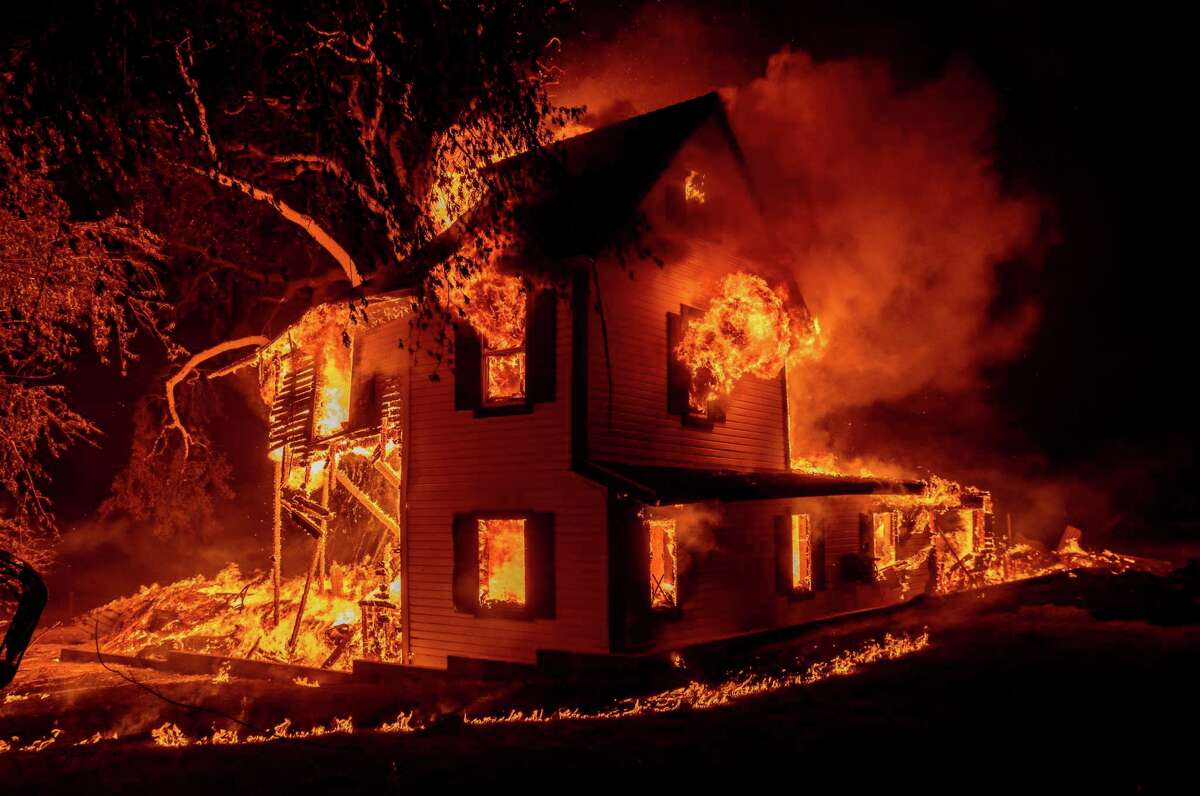 A home burns on Jeters Road as the Dixie fire jumps Highway 395 south of Janesville, Calif., on Monday, Aug. 16, 2021. Critical fire weather throughout the region threatens to spread multiple wildfires burning in Northern California. (AP Photo/Ethan Swope)
