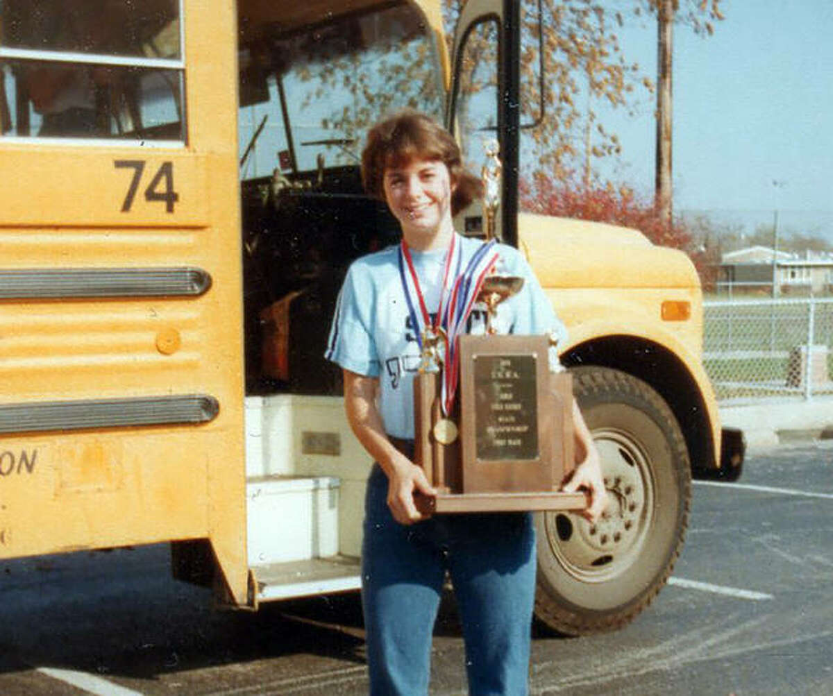 Edwardsville's Amy (Armstrong) Ducharme holds the first-place trophy after EHS won the IHSA field hockey state championship in 1978, when she was a sophomore.