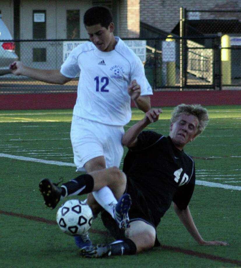 Fairfield Ludlowe's Ian Wolff dodges a tackle by Trumbull's Matt Bundschuh in Tuesday's 1-1 tie at Taft Field. Photo: Tim Parry, Tim Parry For The Fairfield Citizen