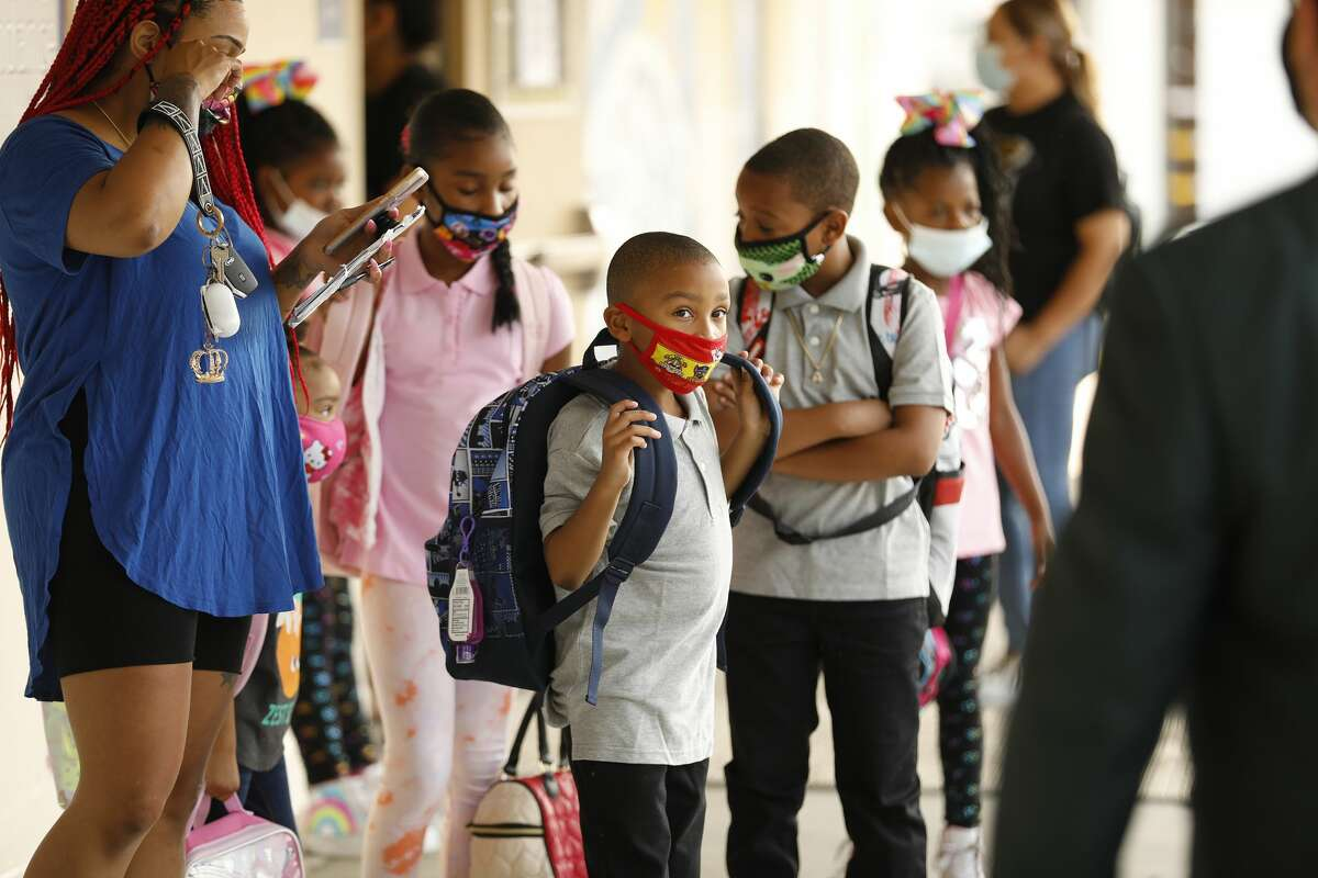 FILE - Mother Ladayna Jordan, left, leads her children, Alayna, Aedan, Aaliyah and Ahmier Davis, left to right, to the front door of Normont Elementary School in Harbor City, CA. (Al Seib / Los Angeles Times via Getty Images).