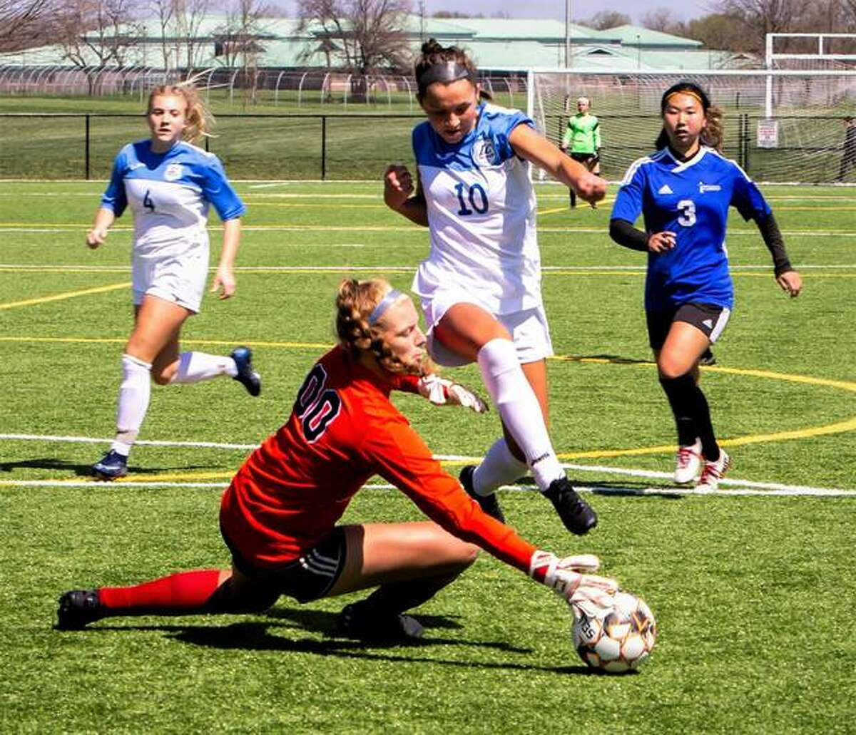 Lewis and Clark's Grace Osvath (10) pressures Eastern Florida State College goalie Marce Thedinga during last spring's rescheduled season at Gordon Moore Park. Osvath, who prepped at St. Dominic's, returns to the LCCC lineup this fall as a freshman because of the NJCAA COVID eligibility grace on players from last school year.