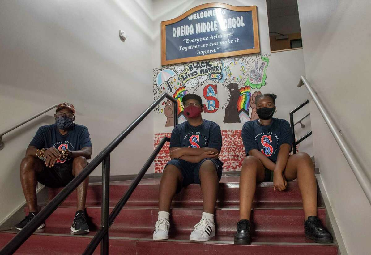 Teacher Yacoba Sangare, left, who leads the Oneida Students for Anti-Racism (OSAR) sits with club members Charles Grant, 13, center, and Jaislyn Loppe, 11, in front of the mural they helped paint at Oneida Middle School on Tuesday, Aug. 17, 2021 in Schenectady, N.Y. They are in line (finalists) to win $25K for their submission to a Neighborhood Assist' contest being run by State Farm Insurance. They need votes to win.