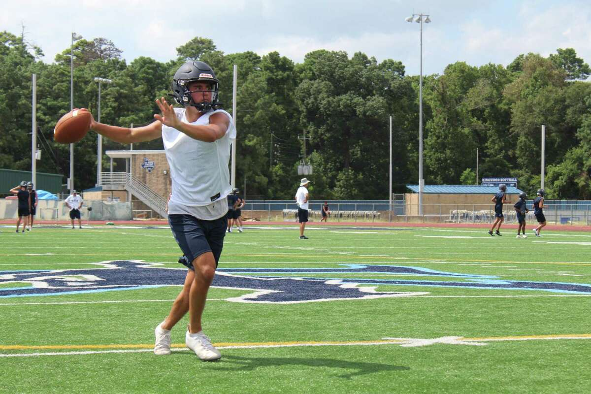 Kingwood quarterback Trey Reese going through drills with wide receivers during the second day of fall camp.