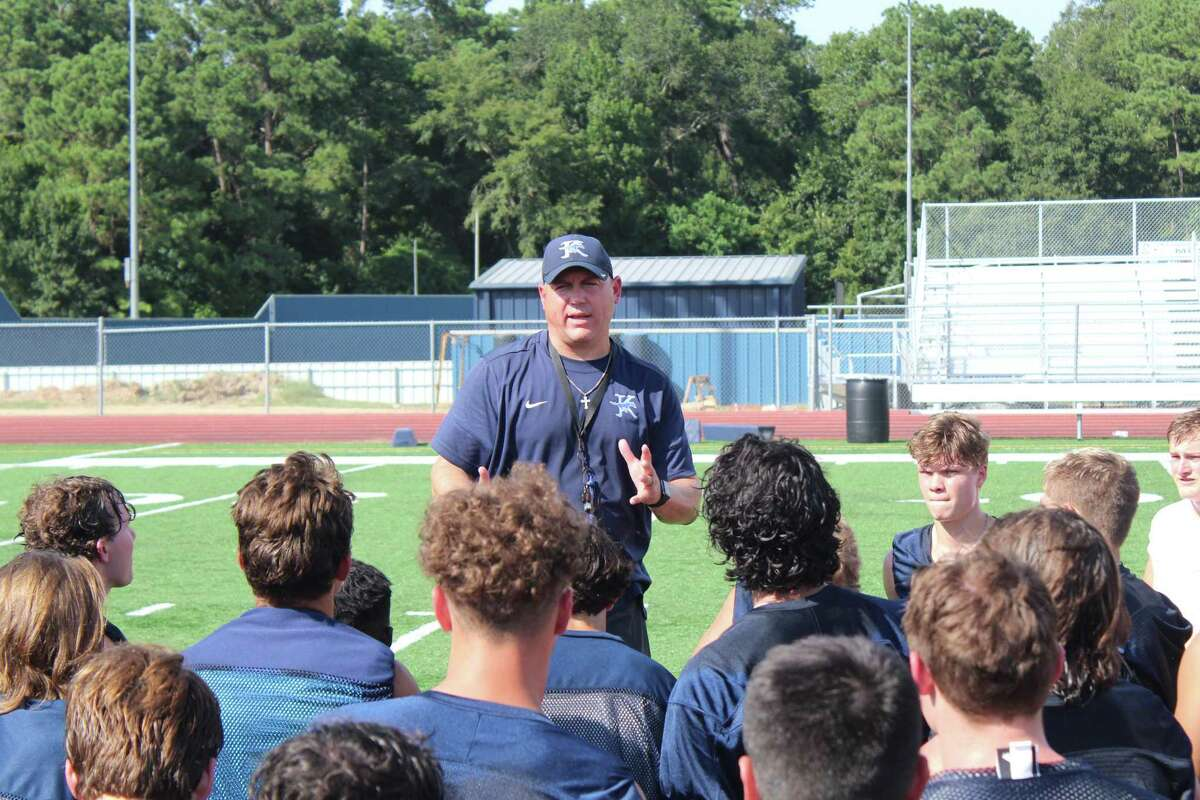 Kingwood coach Cale Melton talking with his Mustangs after the second day of fall camp.