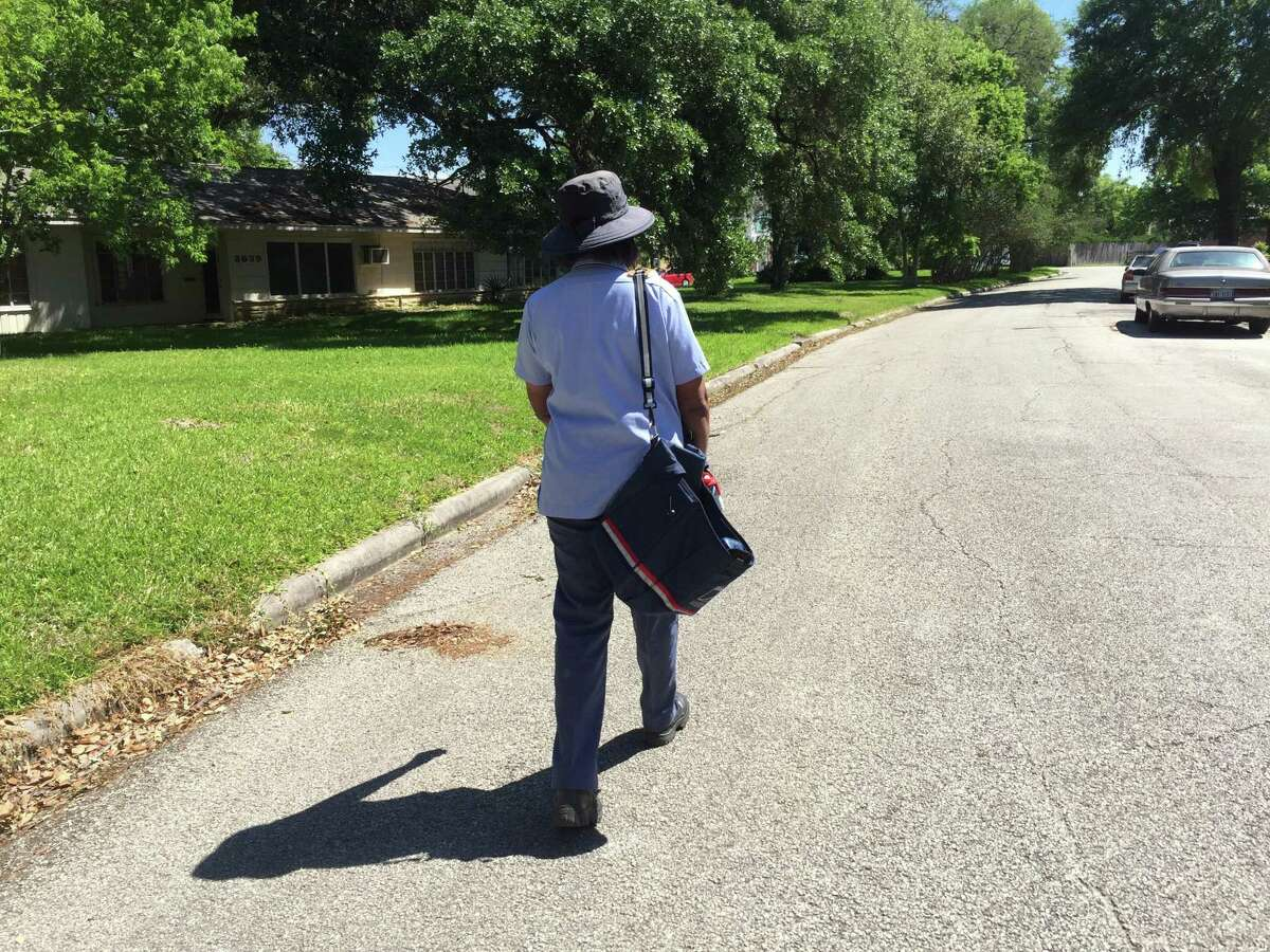 U.S. Postal Service letter carrier is photographed delivering mail in Houston.
