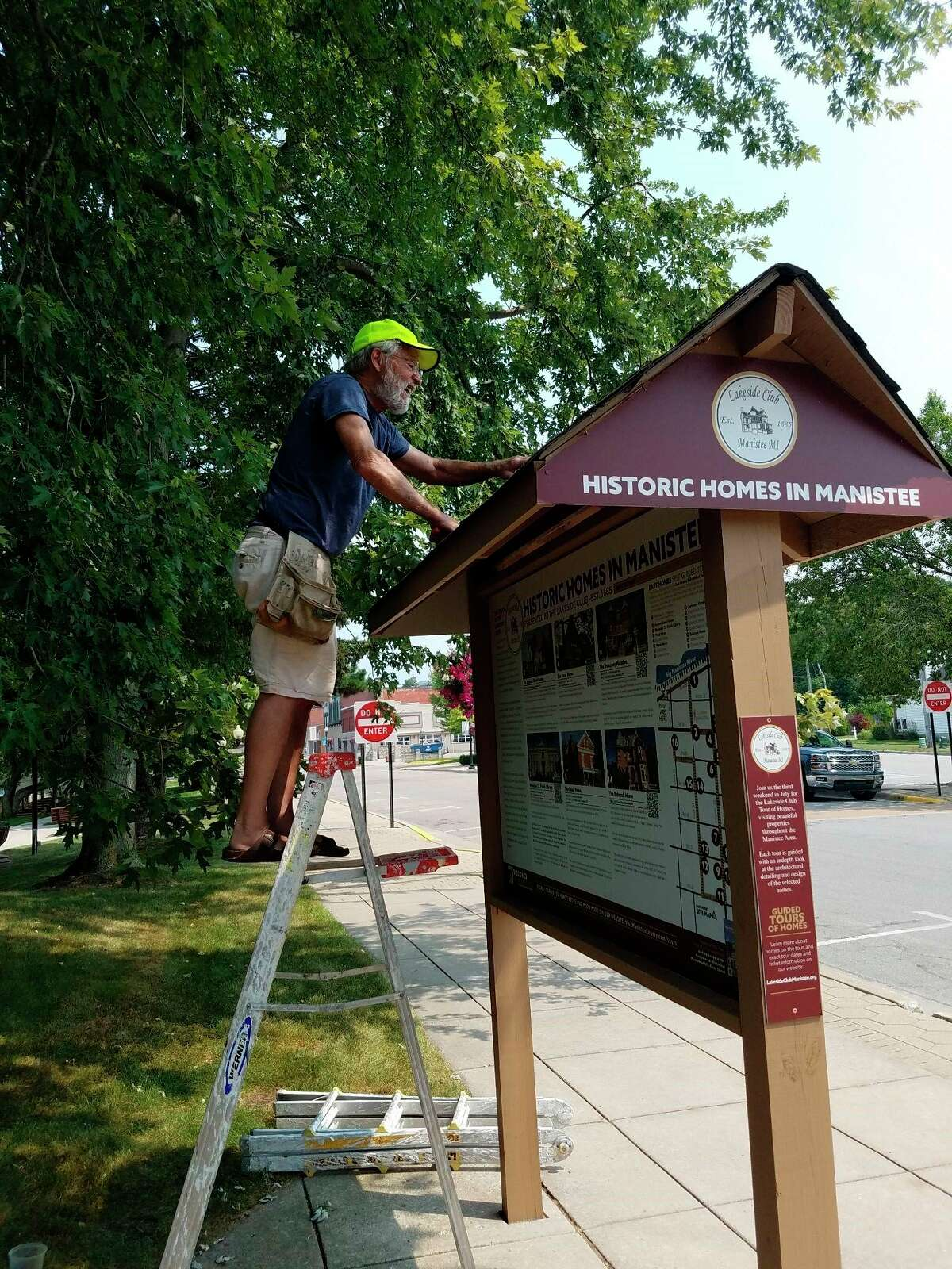 """Josh Swenson puts the finishing touches on the Lakeside Club """"Historic Homes of Manistee"""" on River Street. (Courtesy photo)"""
