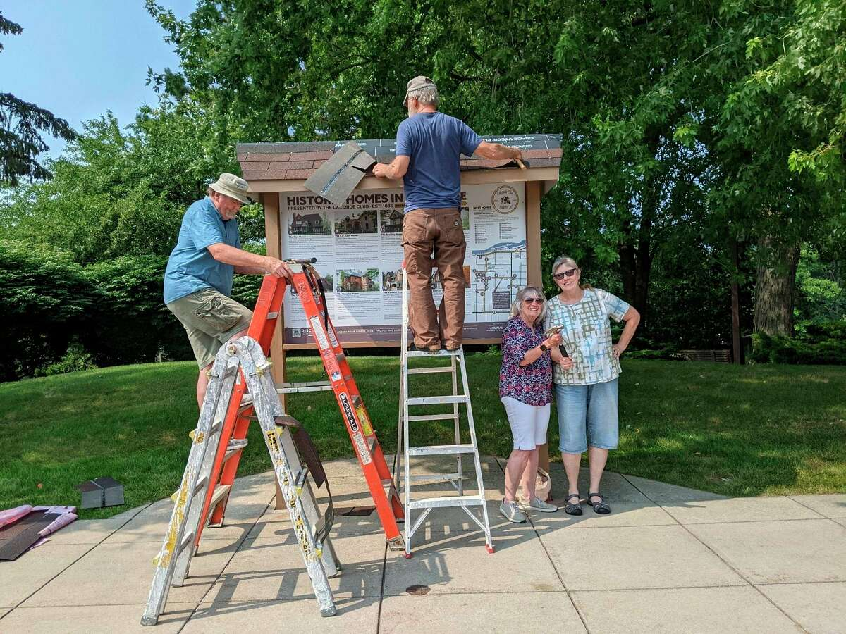 """Gary Madden (left), Josh Swenson, Lynda Beaton and Nanci Swenson complete updates on the Lakeside Club """"Historic Homes of Manistee"""" sign on River Street. (Courtesy photo)"""