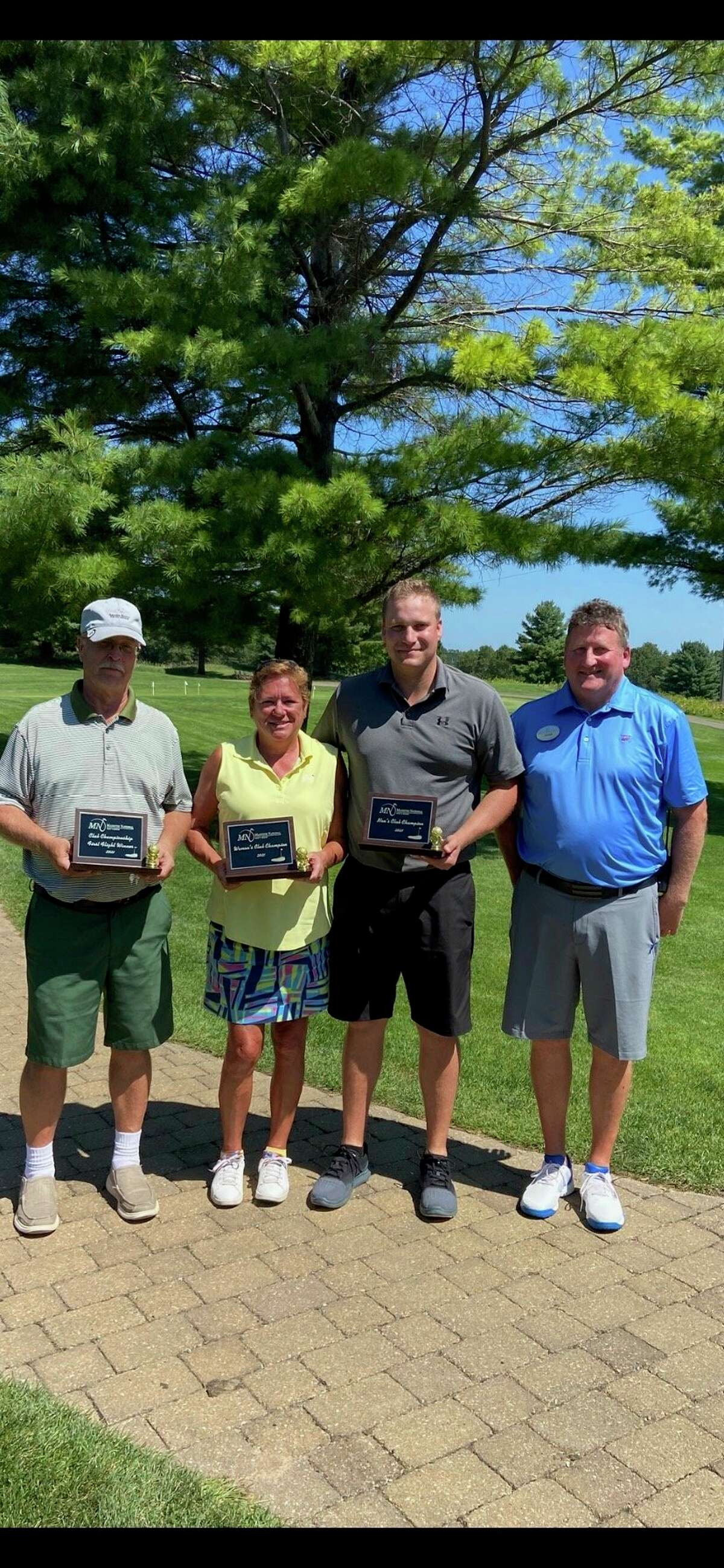 The three (left to right: Mark Niesen, Julie Brakora, and Zach Bialik) Manistee National Golf & Resort Club Championship winners alongside DenisMeikle, the Director of Golf Operations. (Courtesy photo)