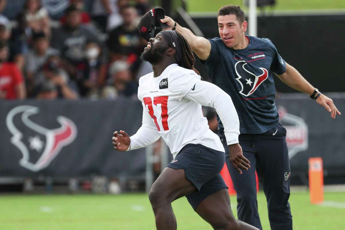 Houston Texans special teams coordinator Frank Ross tries to distract defensive back Tavierre Thomas (37) as he runs up to field a kick during an NFL training camp football practice Friday, Aug. 6, 2021, in Houston.