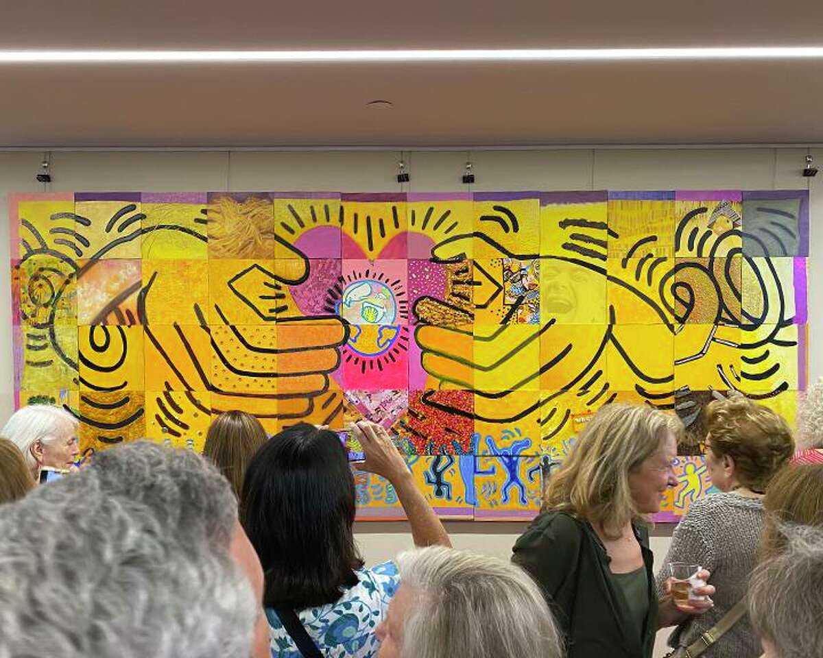 Participating artists and Westport Library staff move in for a closer look after the unveiling of the 5 foot by 12 foot collaborative work of art, inspired by Keith Haring, now on display at the library through Sept. 28, 2021.