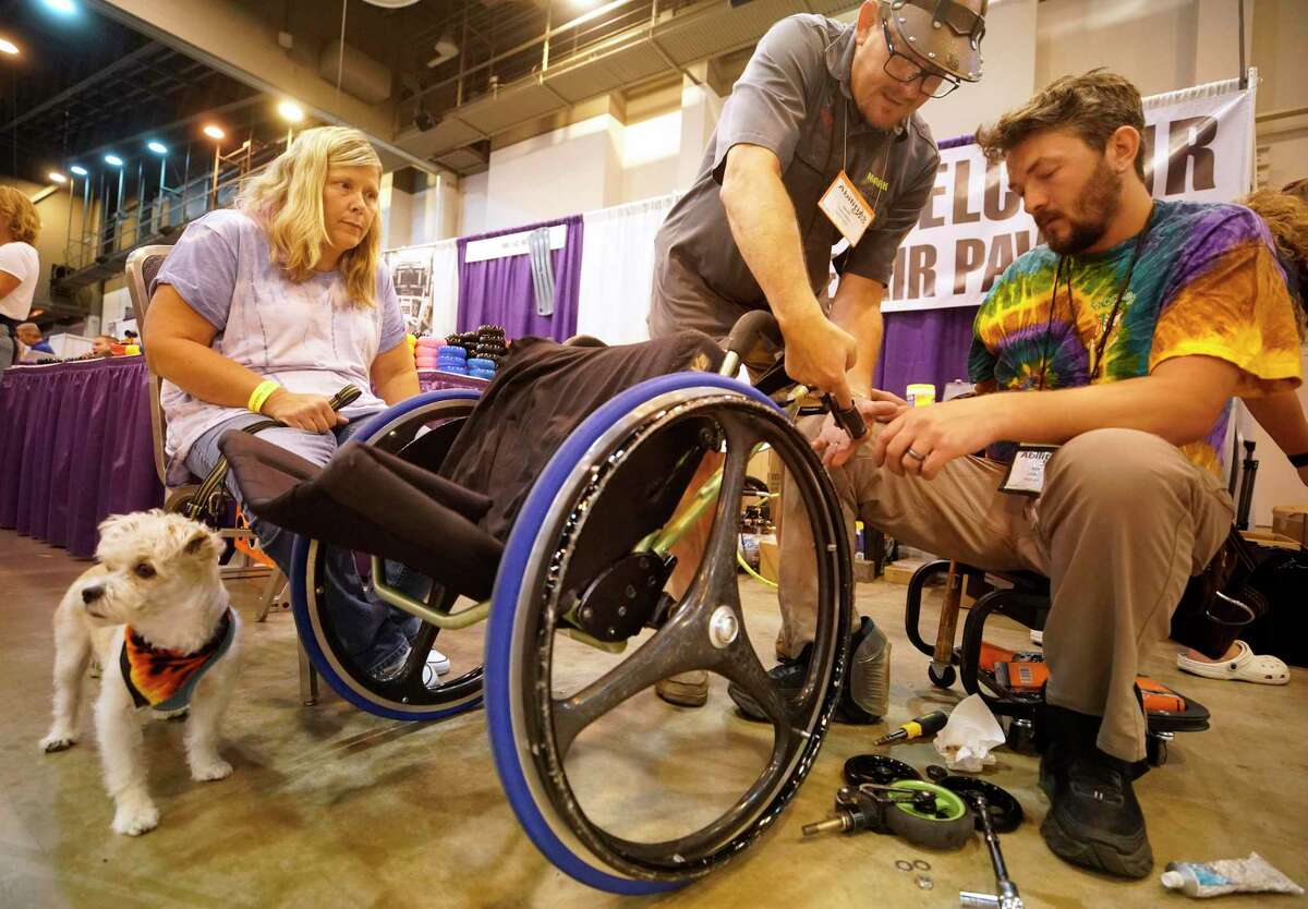 Beth Saffle of Houston, left, waits with her dog, Scrambles, as Mark Chelgren, owner of Frog Legs wheelchair suspension of Ottumwa, Iowa, center, and Ben Cannny, a technician, right, repair her wheelchair during the 2019 Houston Abilities Expo held at Houston's NRG Center.