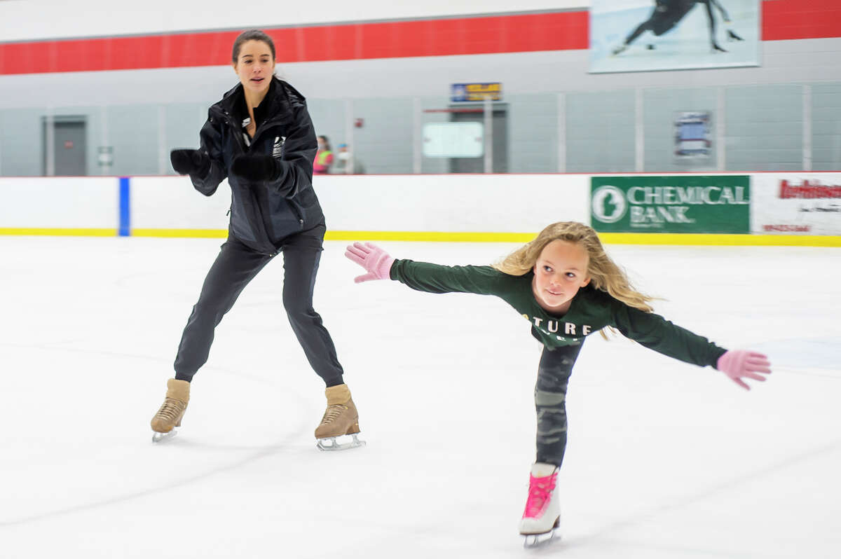 Alissa Czisny, a two-time national women's figure skating champion, left, watches as Avery Martin of the Midland Figure Skating Club, right, works on her skills during a special guest coaching session by Czisny Tuesday, Aug. 17, 2021 at Midland Civic Arena. (Katy Kildee/kkildee@mdn.net)