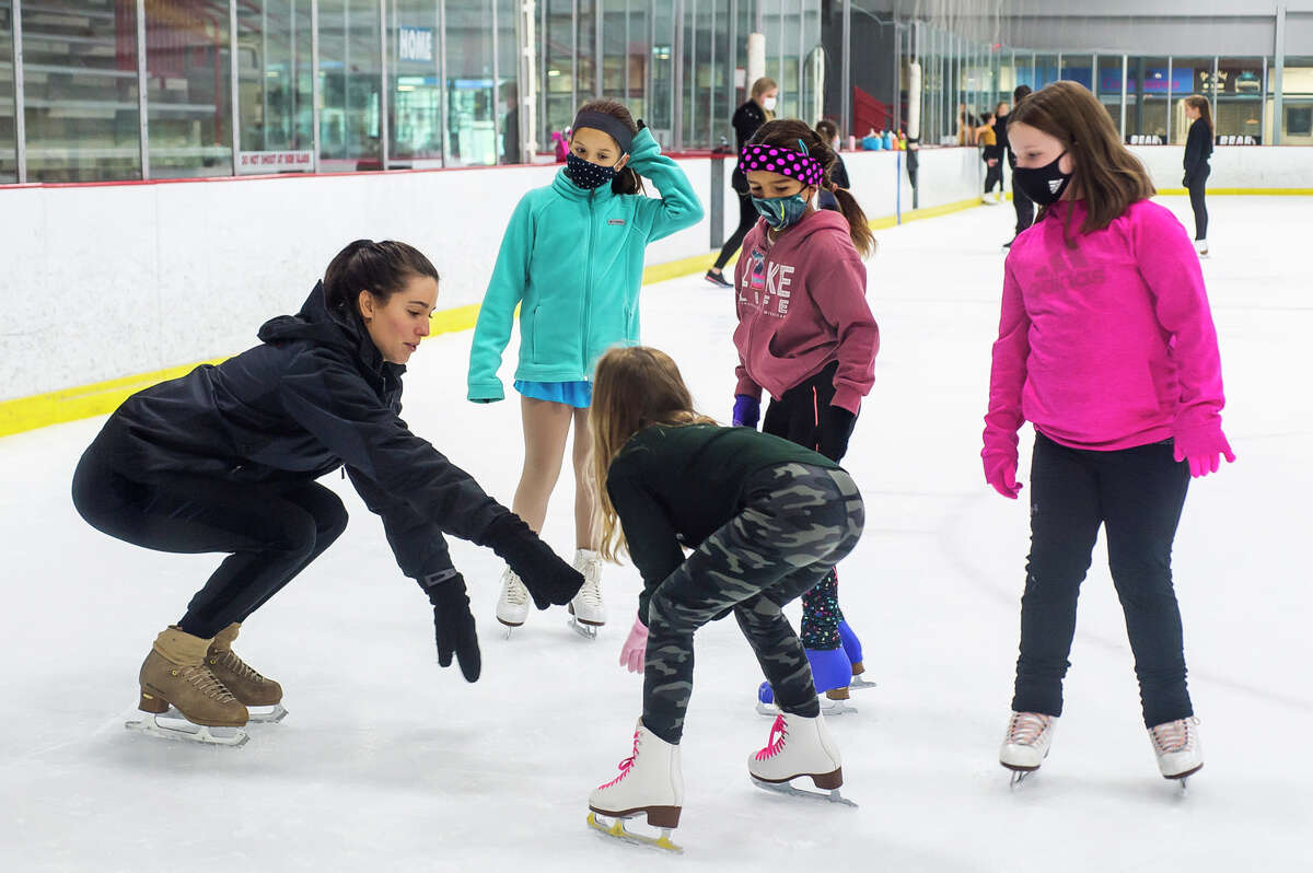Alissa Czisny, a two-time national women's figure skating champion, left, gives instruction to Midland Figure Skating Club members Noa Santos-Claramunt, Avery Martin, Zoe Dhaliwal and Ellie Tarrant during a special guest coaching session Tuesday, Aug. 17, 2021 at Midland Civic Arena. (Katy Kildee/kkildee@mdn.net)