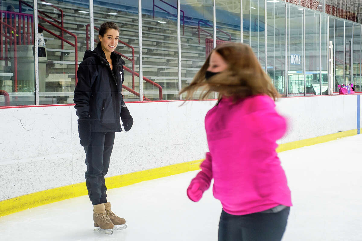 Alissa Czisny, a two-time national women's figure skating champion, left, watches as Ellie Tarrant of the Midland Figure Skating Club, right, practices a spin during a special guest coaching session by Czisny Tuesday, Aug. 17, 2021 at Midland Civic Arena. (Katy Kildee/kkildee@mdn.net)