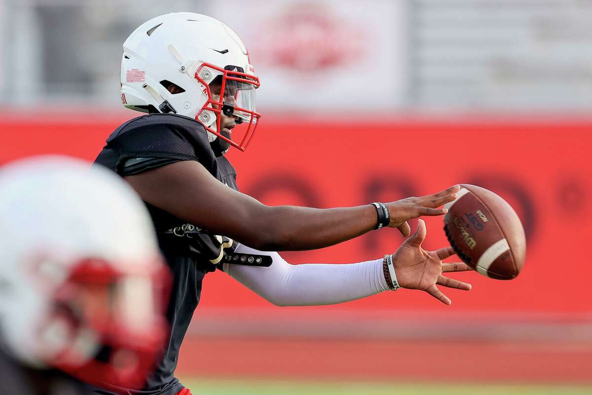 UIW quarterback Cameron Ward takes a snap during a morning practice at Gayle and Tom Benson Stadium on Friday, Aug. 13, 2021.
