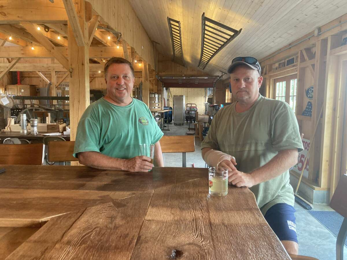 """Chip Kent, left, and Jim Kent enjoy their own home-grown cider. """"We've adapted. Every 40 or 50 years, a company has to renew itself, refresh, do something different. And we're doing something different,"""" Jim said."""
