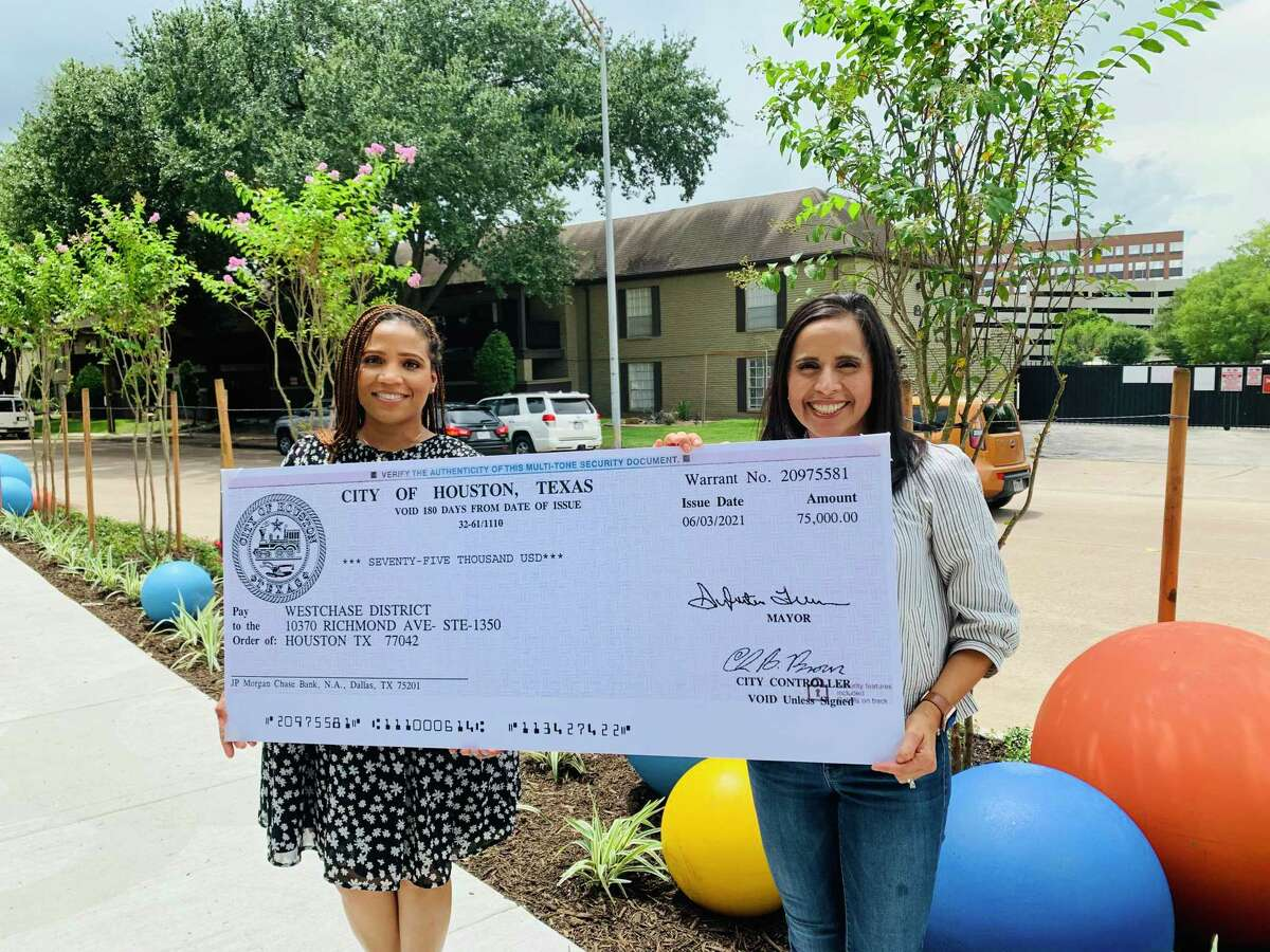 Houston District F City Council member Tiffany Thomas, left, presented a check for $75,000 from her district's public service fund for the Westchase District's Woodchase Drive/Elmside Drive streetscape improvement project tWestchase District Vice President of Projects Irma Sanchez (right).