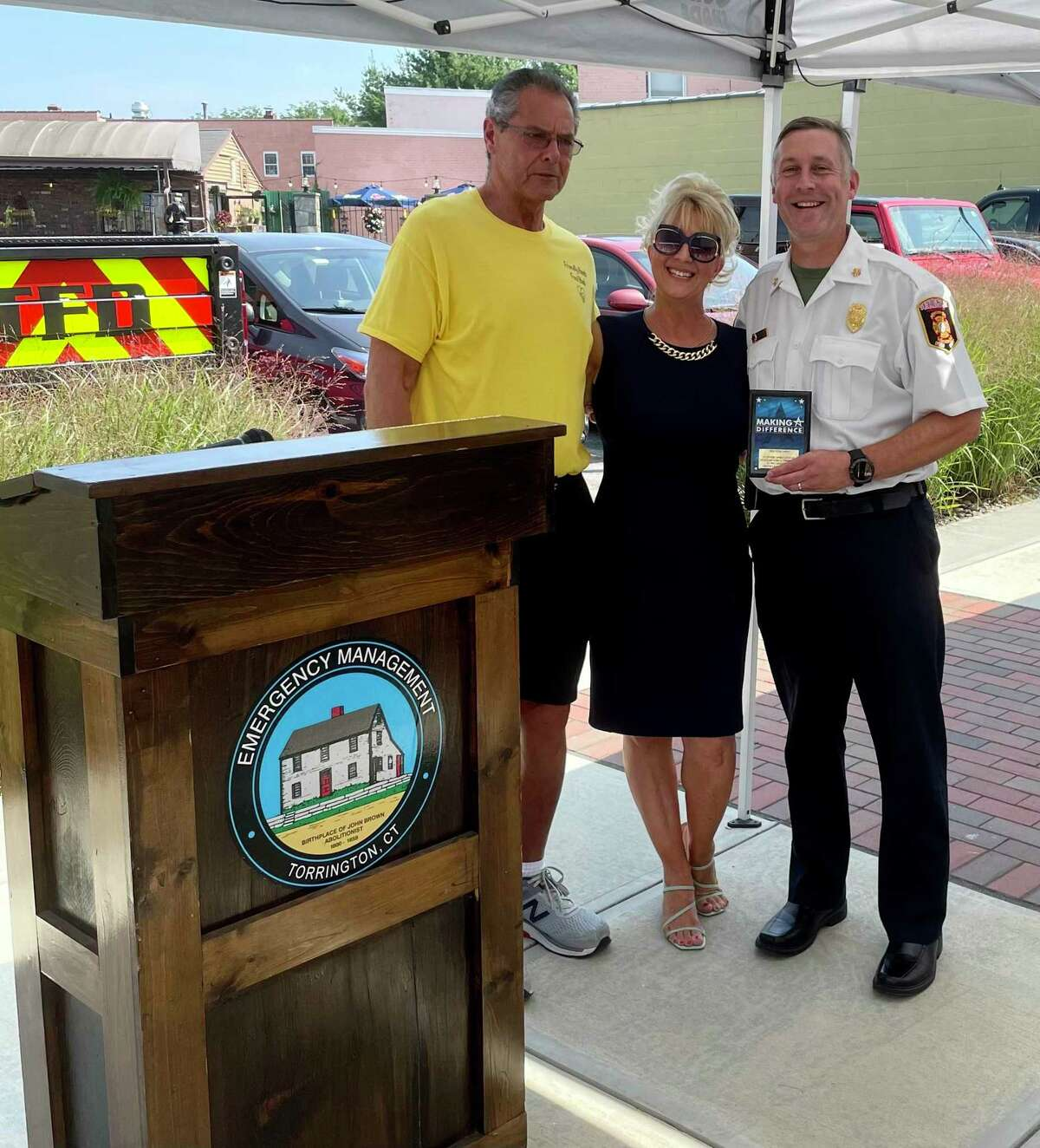 Friendly Hands Food Bank presented outgoing Torringotn Fire Chief Peter Towey with a plaque for his leadership in assisting the food bank with the Farmers to Families Free Food Box Program. The presentatino was made Aug. 13. Food bank board president Danny Hartnett, left, and executive director Karen Thomas, center. presented the plaque to Towey.