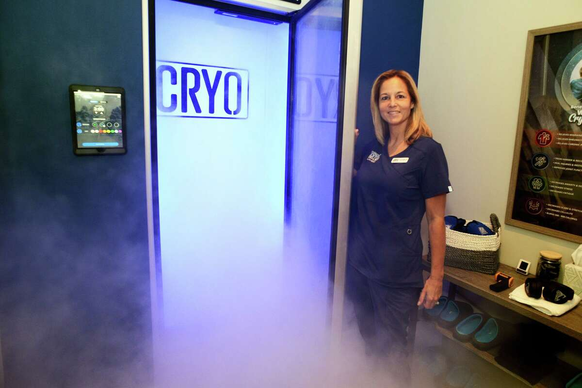 Tracey Miller poses next to the whole-body cryotherapy chamber at iCRYO Recovery & Wellness, in Fairfield, Conn. Aug. 17, 2021.